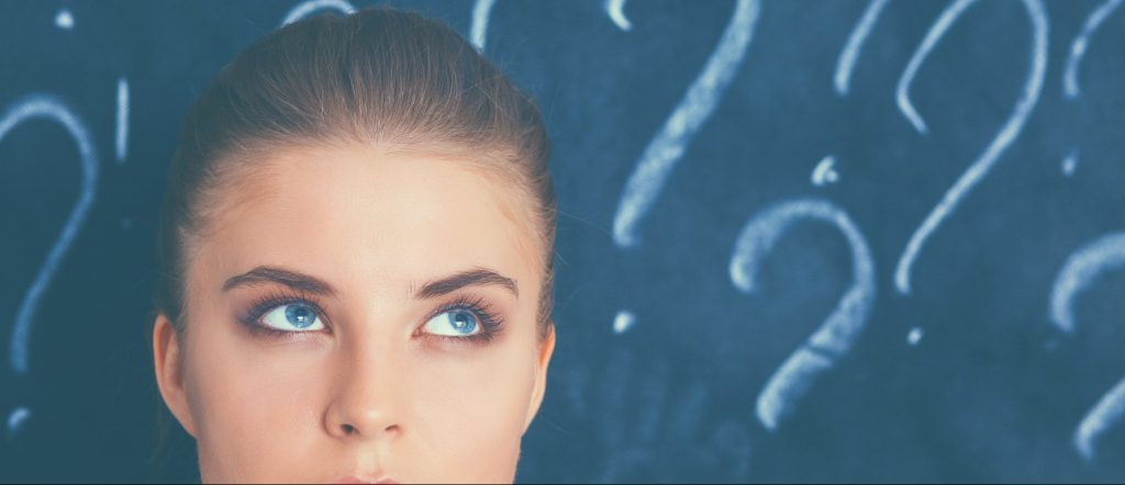 woman in front of chalkboard with question marks