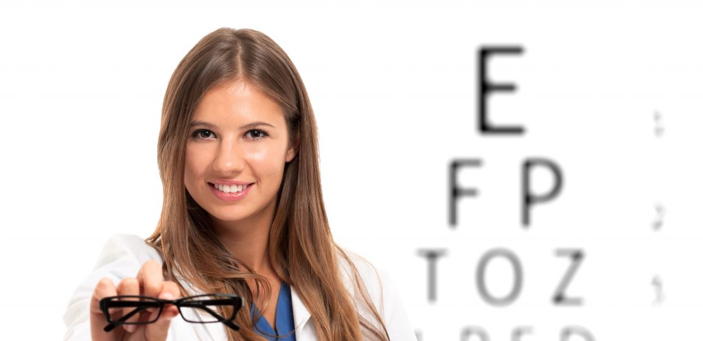 woman holding glasses in front of blurry eye chart