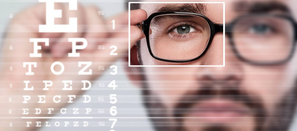 man in glasses looking at eye chart