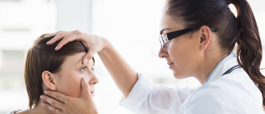 Eye care doctor looking at person's eyes