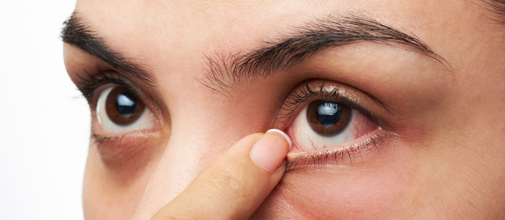 woman holding open her eye with her finger