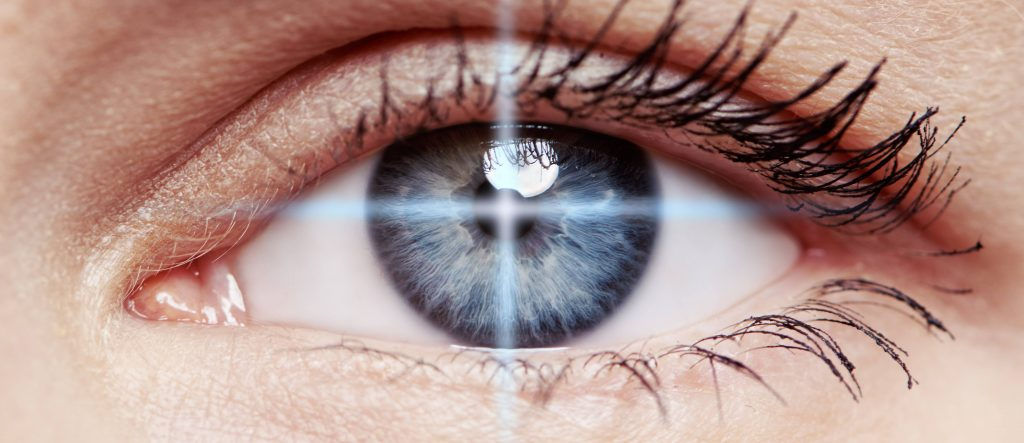 close up of woman's blue eye with retical