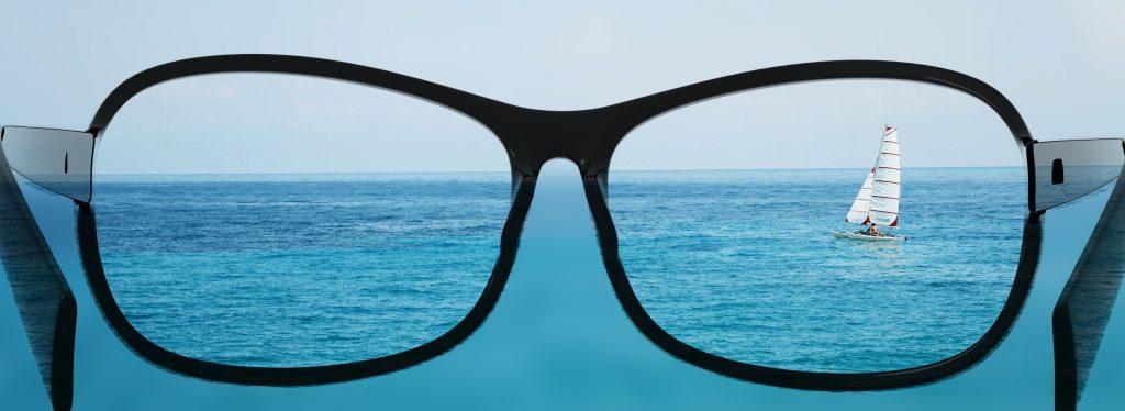 glasses looking at sailboat in the ocean