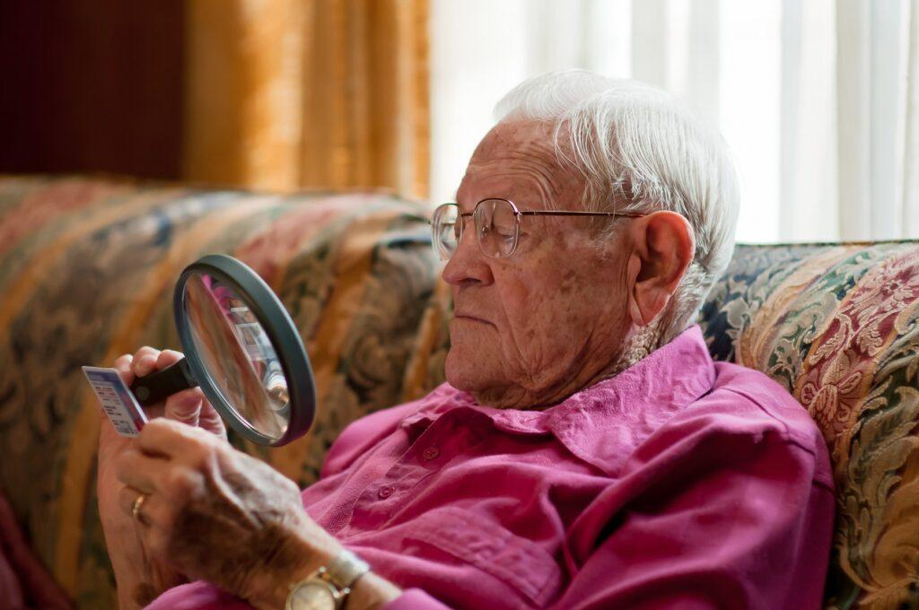 elderly man looking at object with magnifier