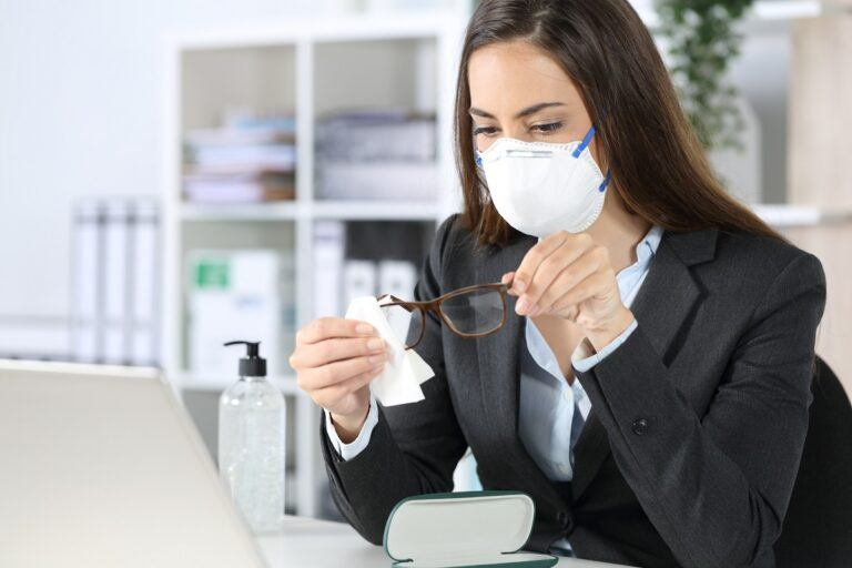 executive with mask cleaning glasses with sanitizer