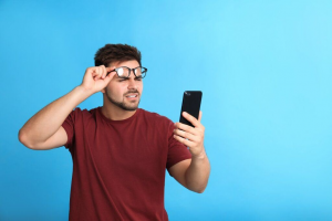 young man with vision problems using smartphone