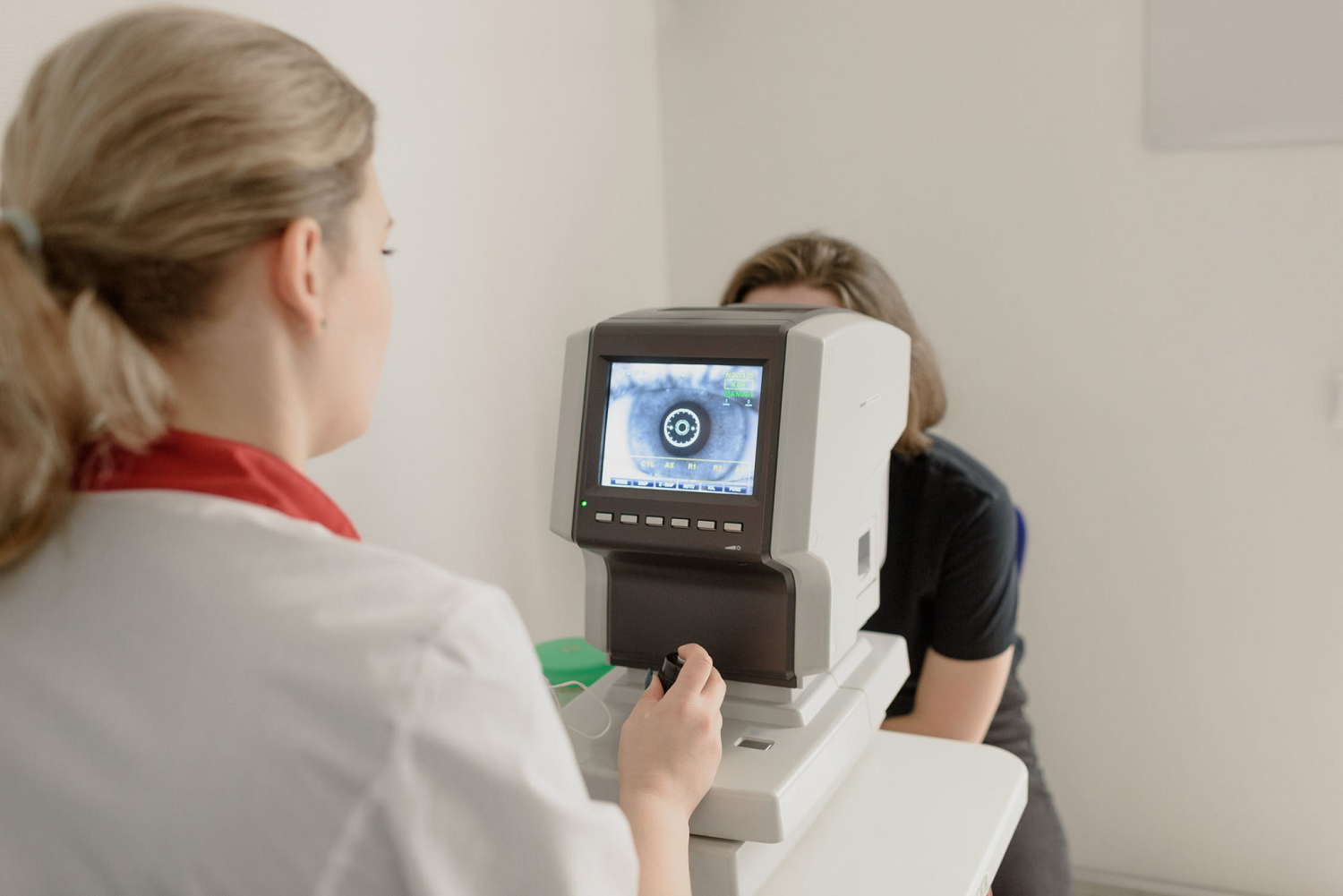 ophthalmologist checking eyesight of woman on vision screener