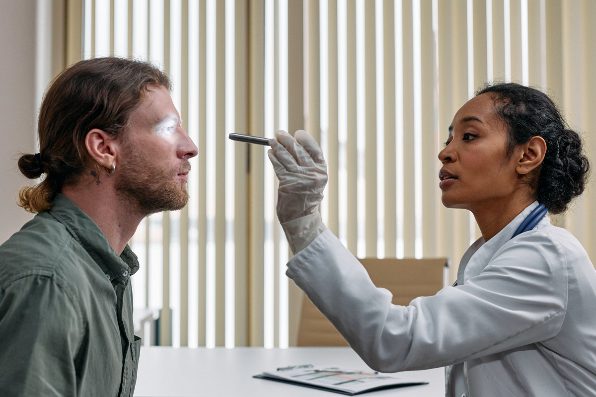 Female doctor examining patient's eyes