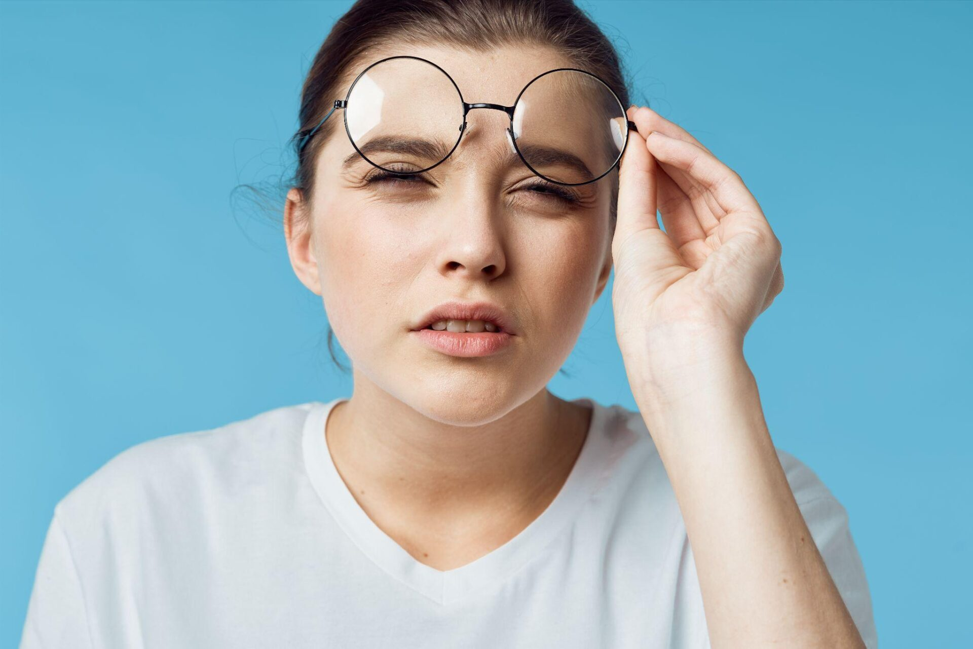 The woman's eyes narrowed vision problems glasses in her hand